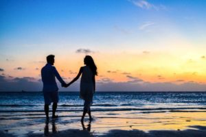 Couple walking in the beach,hand in hands under a beautiful sunset