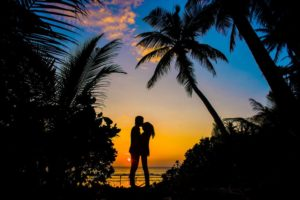 a couple kissing under a sunset and promising not to judge one another