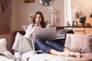 Girl sitting comfortably in her sofa and smiling over a text